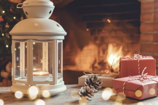 Lantern with a burning candle, gifts on a wooden table in a room with a Christmas tree and a fireplace on Christmas Eve.