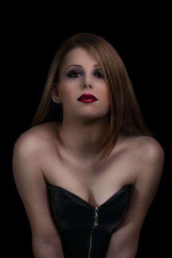 Low key make up and beauty portrait of a sensual young woman with red lipstick on black background.