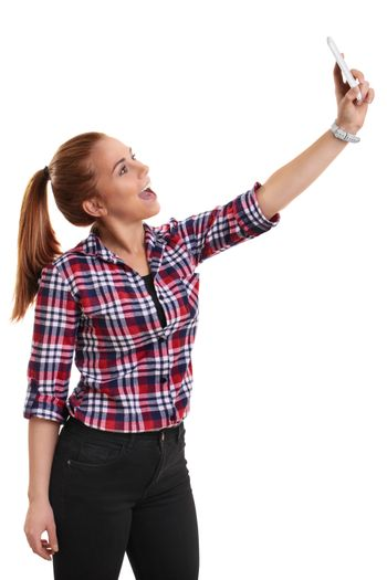 Smiling beautiful young girl dressed in casual clothes taking a selfie, isolated on white background.