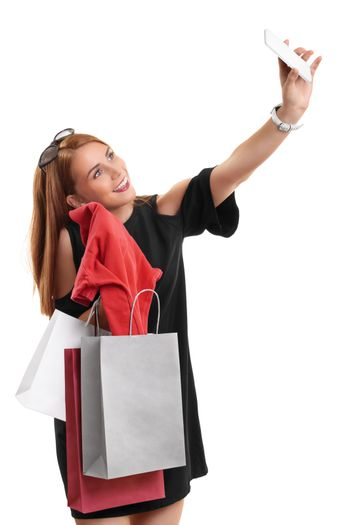 Beautiful smiling young girl taking a selfie with her shopping bags and her new clothes, isolated on white background. Shopping, buying concept.