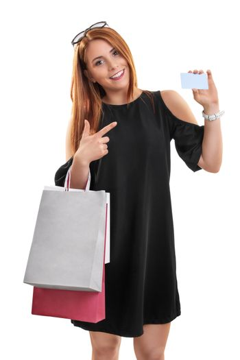 Portrait of a beautiful young girl in a stylish dress holing shopping bags and pointing to a blank card, isolated on white background. Shopping concept, copy space.