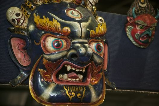 Traditional oriental blue and gold mask that looks terrifying and combative.