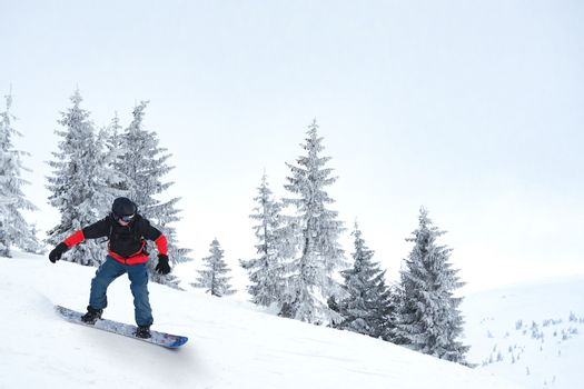Snowboarder Riding Snowboard in Mountains. Snowboarding and Winter Sports