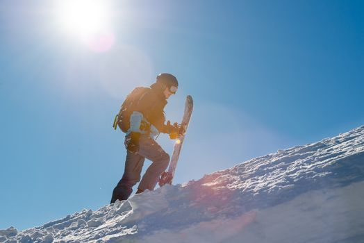 Snowboarder Climbing up with Snowboard in the Mountains at Sunny Day. Snowboarding and Winter Sports