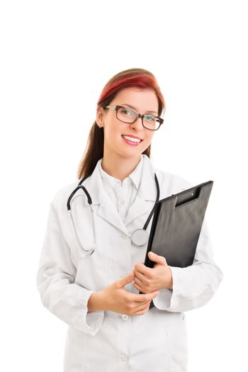 It's all fine. We are here for you. Portrait of a smiling young female health care professional or doctor or nurse with glasses and a stethoscope, holding a clipboard, isolated on white background.