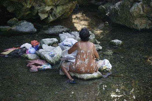 Katiklan, Philippines - October 24, 2008: Filipino elderly woman washing clothes in the river. Philippines. Island Katiklan