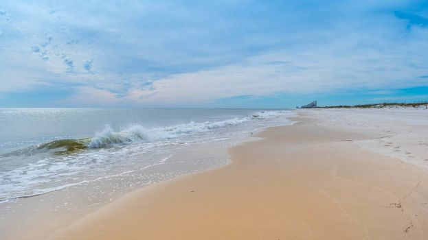 A beautiful sea whitecap waves roll onto the sandy beach of Pensacola