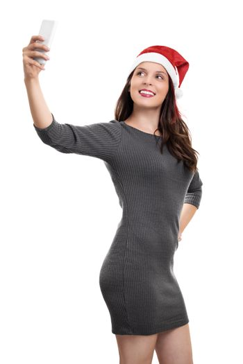 Portrait of a young beautiful girl in a dress with Santa's hat taking a selfie, isolated on white background. New Year or Christmas selfie.