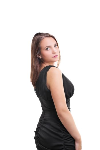 Portrait of a young beautiful woman in a black dress looking back over her shoulder, isolated on white background.