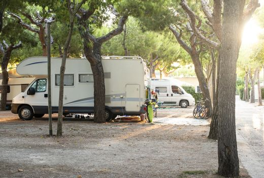 White camper on campsite. Sun Rays in the morning through the trees. Many bikes and caravans in camping.