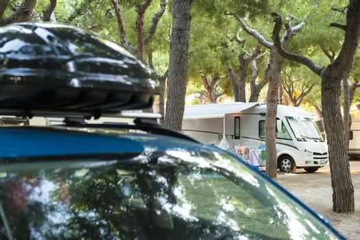 Car with luggage box on top. Camper on background in campsite. Recreation concept in camping.