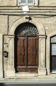 Old typical italian wooden door. Italian house. Ancient house facade. Sunlight. Round door arch. Stone build house. Wrought iron door handles.