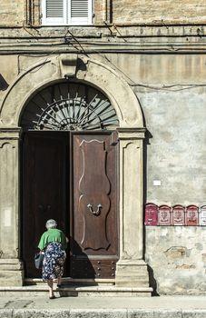 Senior woman enter in the house. Old typical italian wooden door. Italian house. Ancient house facade. Sunlight. Round door arch. Stone build house. Wrought iron door handles.