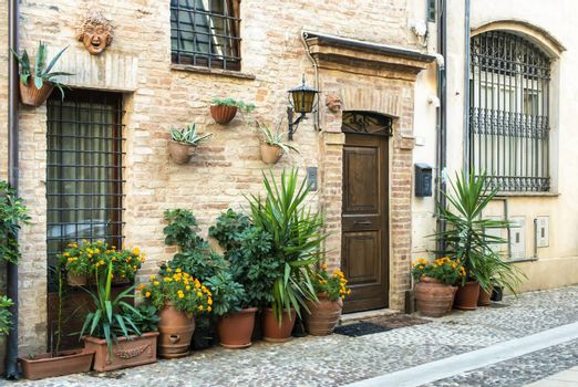Old buildings on small italian street. Narrow street in Italy. Flowers in front of vintage houses.