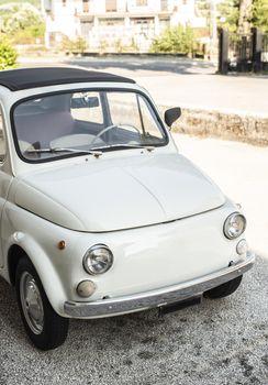 Small italian vintage car. White car.