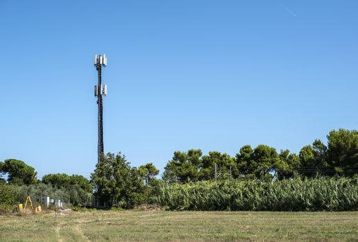 Telecommunication 5G transmitters. GSM antenna on blue sky. Antenna in the nature. New 5G technology concept. Green foliage and trees.