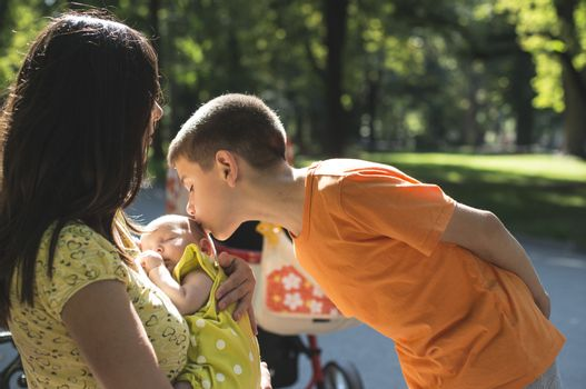 Women, brother and baby in a park. Child kissing baby