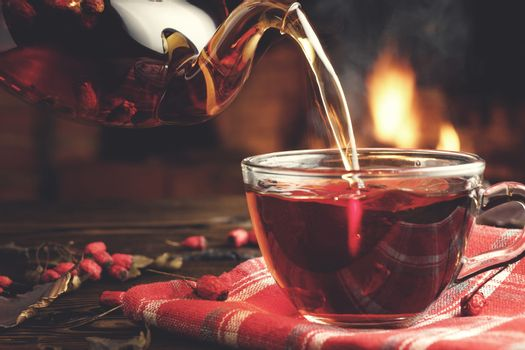 Pouring hot tea with hawthorn into a glass cup in a room with a burning fireplace in the background.