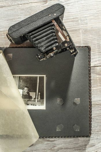 Vintage photo camera and album on white wooden background