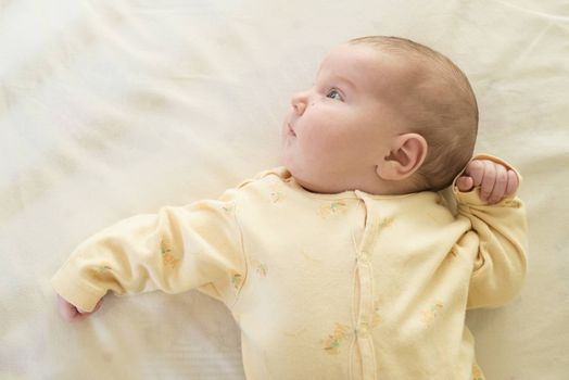 Baby in a baby bed. White clothes. Window light