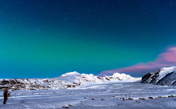 Man taking pictures of amazing view on night starry sky in Iceland, enjoying Northen Lights landscape, active winter traveling, wildlife ladscape photographer