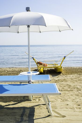 Blue sunbeds and umbrellas on the beach.