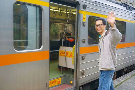 Asia man Traveler feeling happiness and greeting his friend before getting on the train at the Pingxi Line historic train station in Taiwan . Travel and transportation concept.