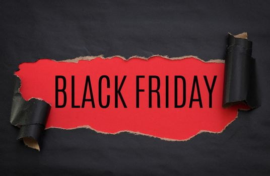 Black torn paper and text black friday on a red background