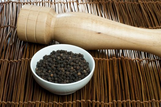 Bowl with black pepper and wooden pepper mill