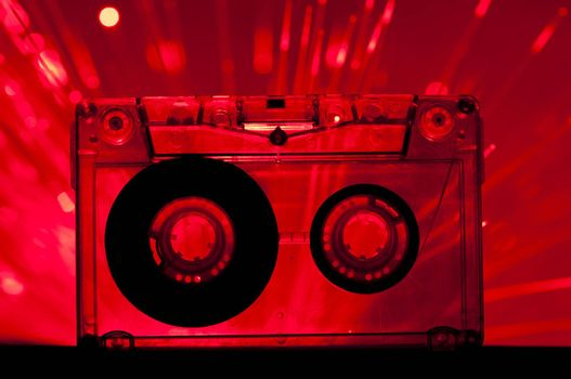 Transparent Cassette tape and red color disco lights background