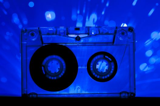 Transparent Cassette tape and blue color disco light background