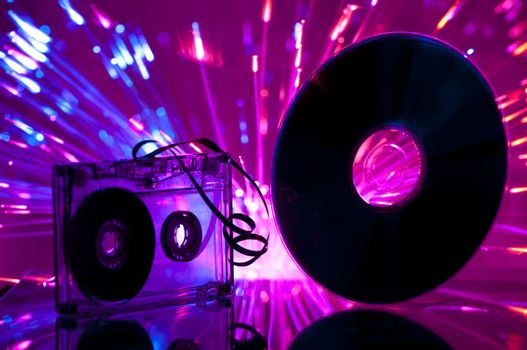 Cassette tape and CD. Multicolored blue lights on background