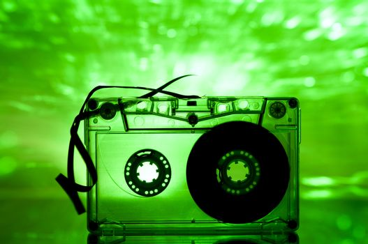 Cassette tape and multicolored green lights on background