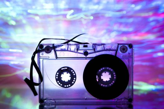 Cassette tape and multicolored pink blue lights on background