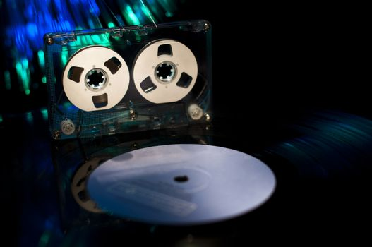 LP vinyl record, cassette tape and disco lights on background