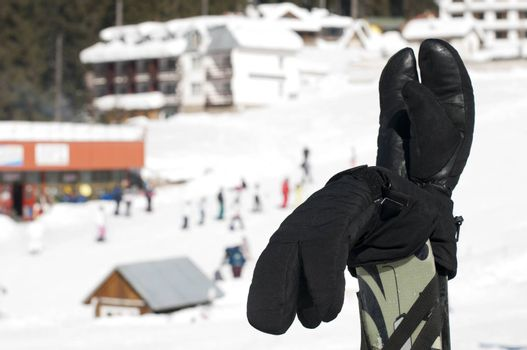Ski gloves and sticks. Winter tourists on the background.