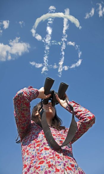 Woman watching with binoculars.Dollar symbol on sky