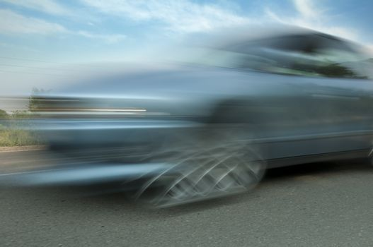 High speed blurred car with blue sky
