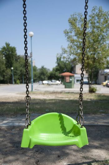 Empty green swing with chain. Vertical image