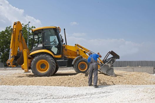 Worker and gravel excavator on blue sky