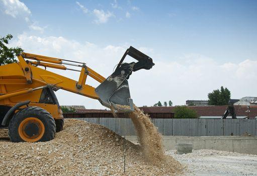 Yellow excavator unload gravel