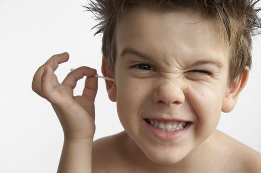 Boy cleans his ear. Isolated white background