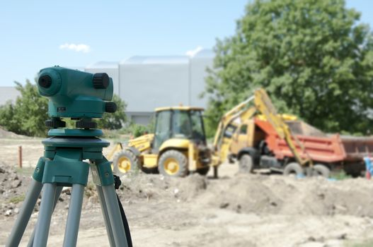Surveying equipment to the construction site. Excavator and truck on the background