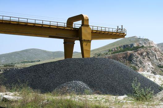 Balck asphalt pile and crane in quarry