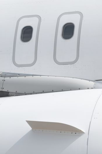 Windows of an airplane outside. White color plane. Vertical image