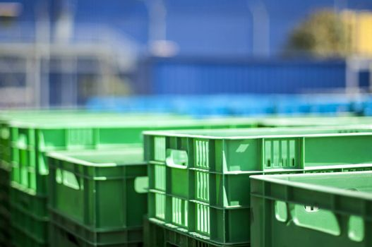 Green plastic crates. Blurred blue background