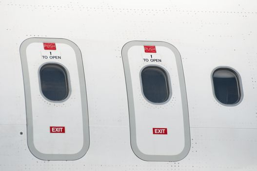 Windows of an airplane outside. White color plane. Two doors