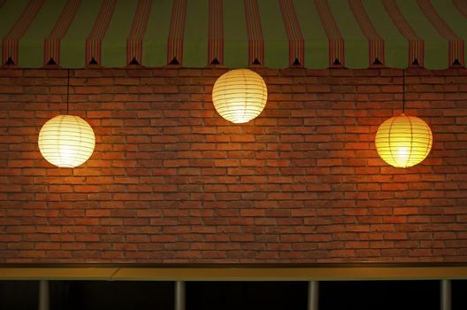 Brick wall with three illuminated lamps. Lighting