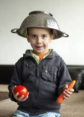 Boy with tomato and carrot in hand. Vertical image