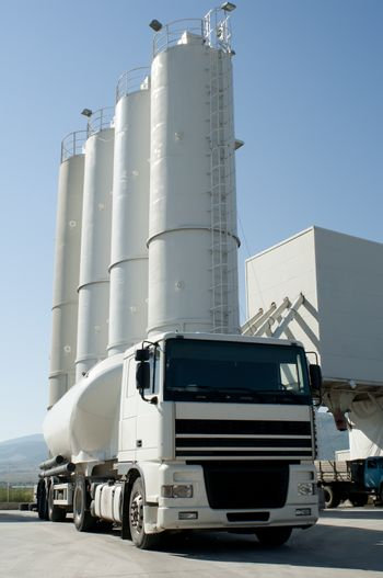 Cement factory with silos and white mixer truck